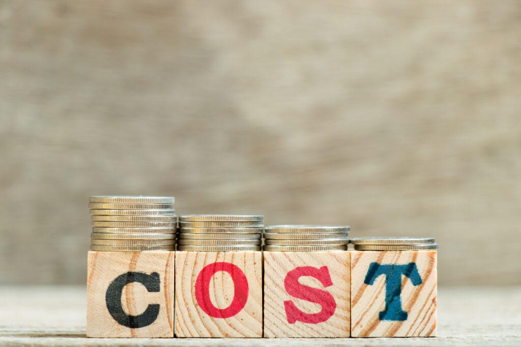 「COST」と書かれた積み木の上にコインが乗っている