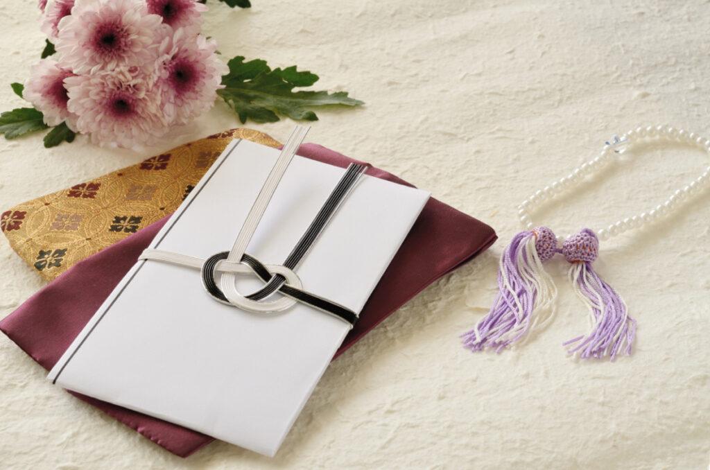 ピンク色の菊と白黒の水引の封筒と数珠