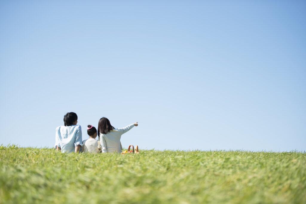 青空の下で草原に座っている親子3人