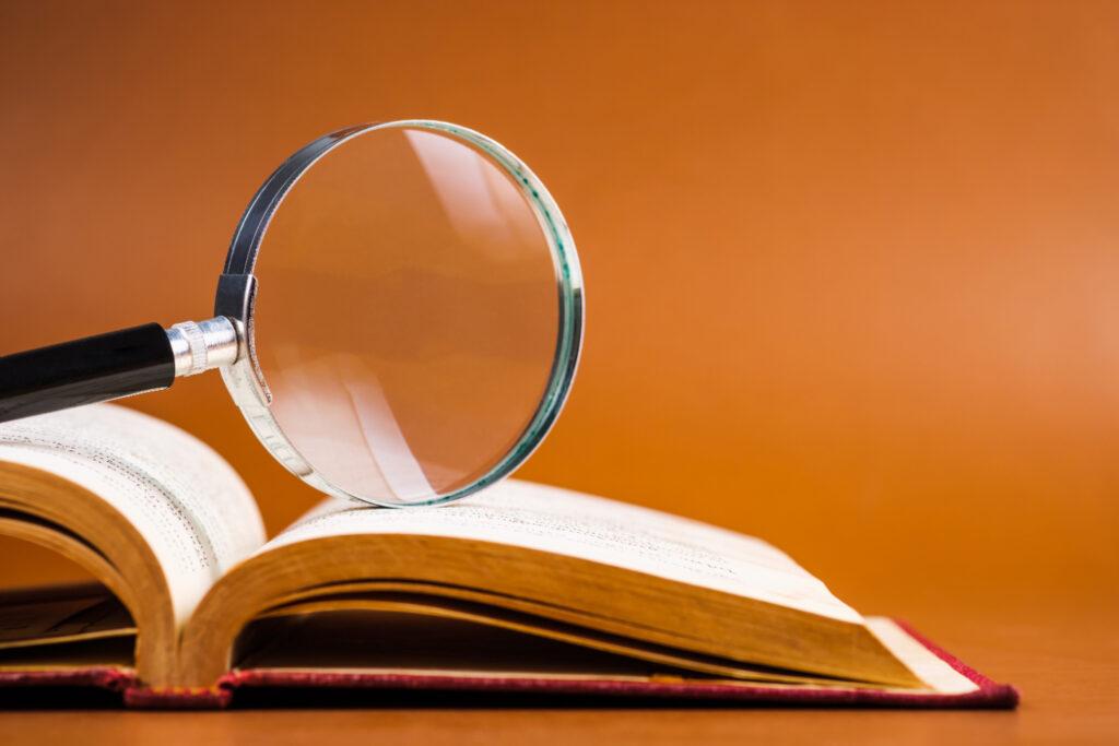 開いた本の上に置かれた虫眼鏡