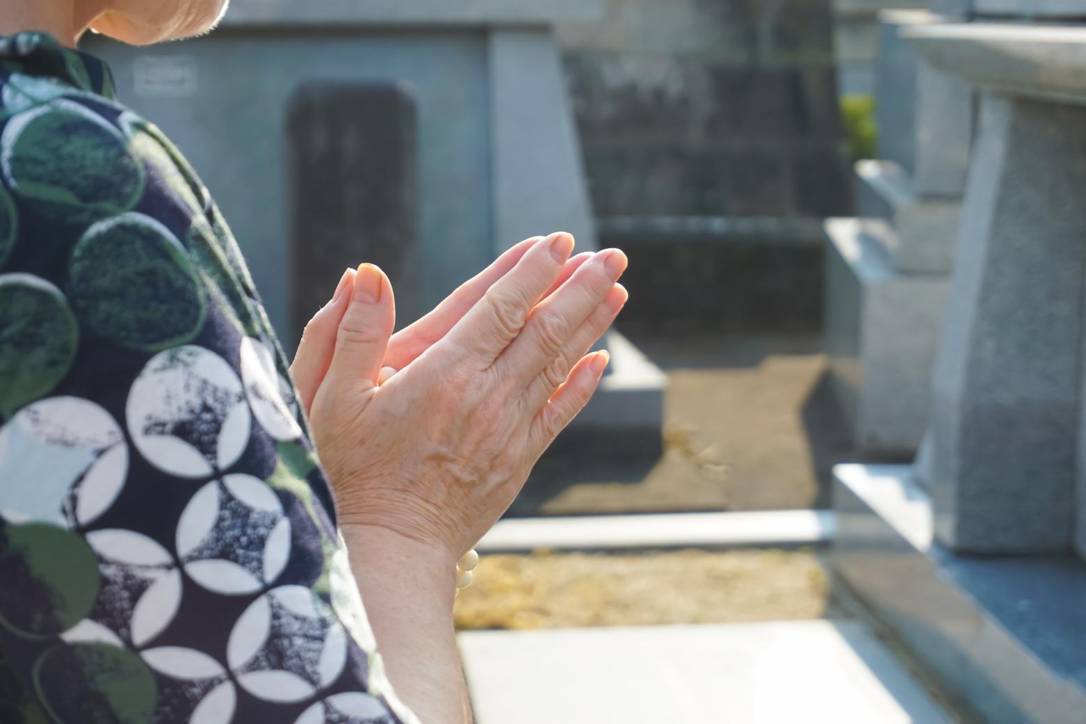 お墓の前で手を合わせる高齢の女性の手元