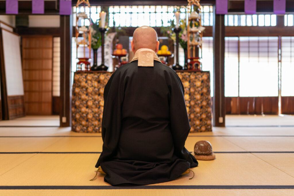 仏壇に向かって祈りをささげる僧侶の背中